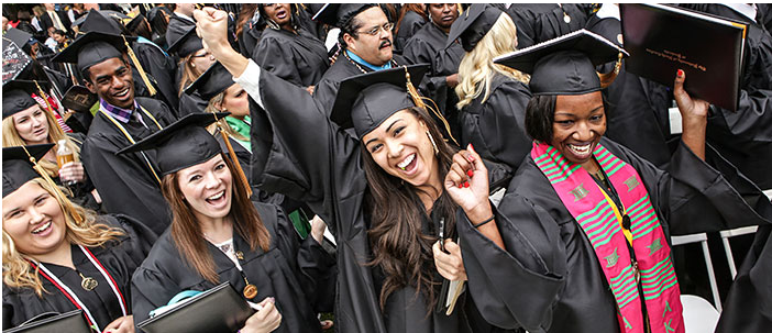 A large, diverse group of students celebrate their graduation by standing up, high-fiving each other, smiling and embracing